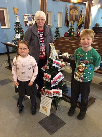 Maureen, Storm and Junior with their Christmas tree decorated for Kiri and DKMS